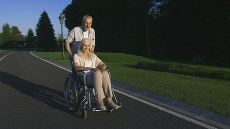 Man pushing his wife in her wheelchair