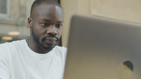 Man reacts in pain to news on laptop