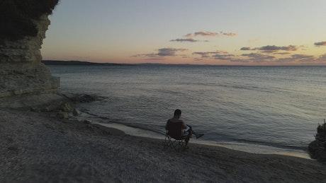 Man reading a book near the seashore
