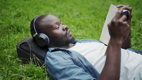 Man reading while listening to music in the park