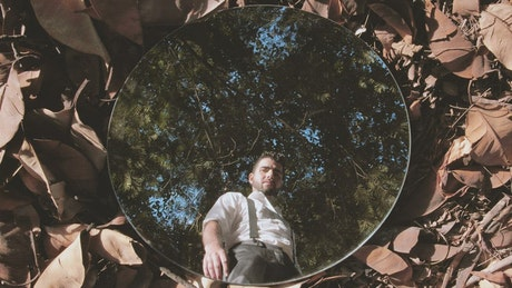 Man reflected in a mirror on dry leaves