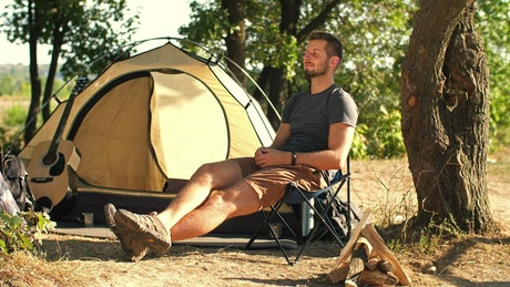 Man relaxing in his camp in nature