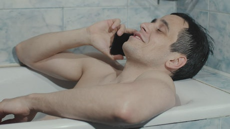 Man relaxing on the phone in the bathroom