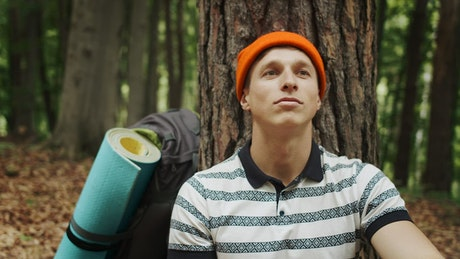 Man resting in a forest with hopeful attitude