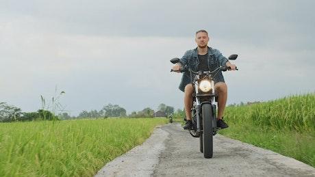 Man rides motorcycle chopper on farm field path