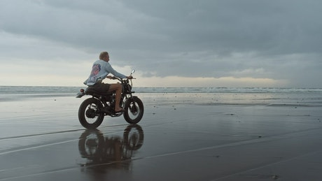 Man riding motorcycle on the beach on a cloudy day