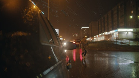 Man runs to get in his car on a rainy night