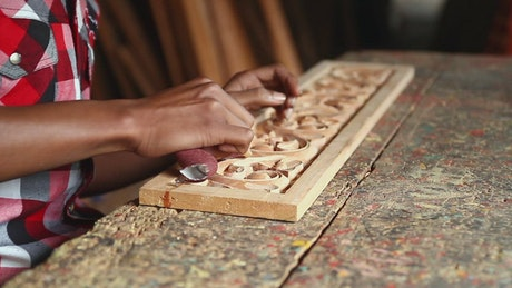 Man sanding a wooden carving