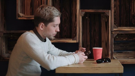 Man scrolling through his phone in a cafe