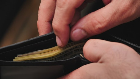Man searching for a banknote in his wallet close up view