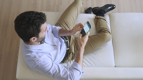 Man sending a text message while relaxing