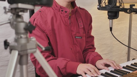 Man shooting a video singing and playing the piano