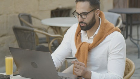 Man shops online in cafe and pays with credit card