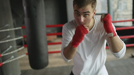 Man shows off boxing moves with red handwraps