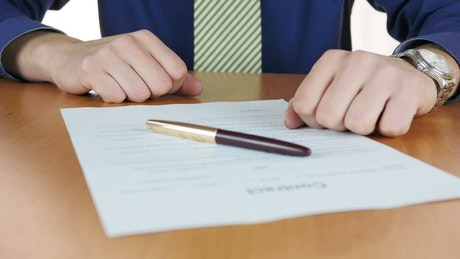Man signing a contract with pen