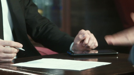 Man signing off a contract and handshake