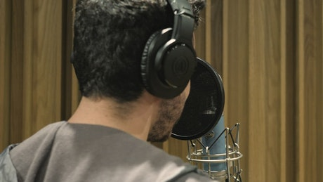 Man singing in a recording studio