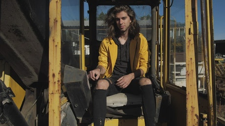 Man sitting among yellow rusty tubes