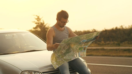 Man sitting in his car looks at a map on the road