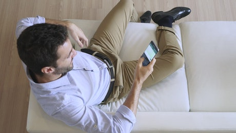 Man sitting on a sofa chatting on his cell phone