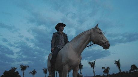 Man sitting on white horse