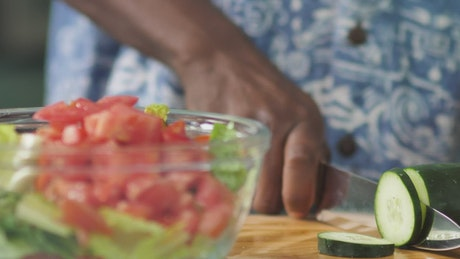 Man slicing cucumber for salad