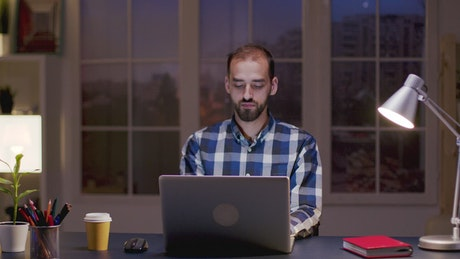 Man smiles while thinking and working from home