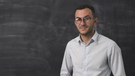 Man smiling by a blackboard