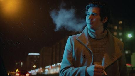 Man smoking in the street on a light rainy night