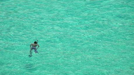 Man snorkeling in crystal waters