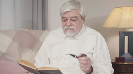 Man spends an evening smoking pipe and reading
