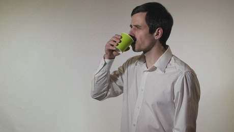 Man spills his drink while drinking it