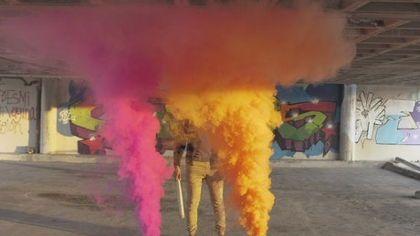 Man standing between colorful smoke bombs