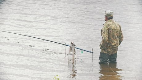 Man standing in a lake with a fishing rod