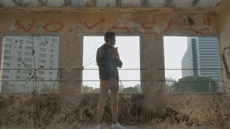 Man standing outside abandoned building