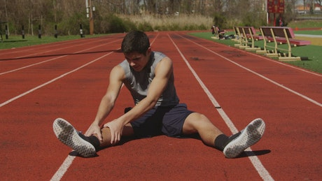 Man stretching at a running track