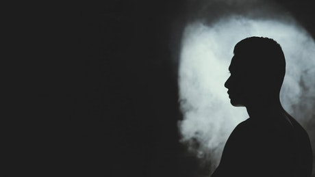 Man stretching in the dark and smoke