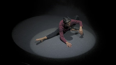 Man stretching in the spotlight