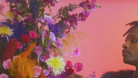 Man stroking the petals of a large flower arrangement