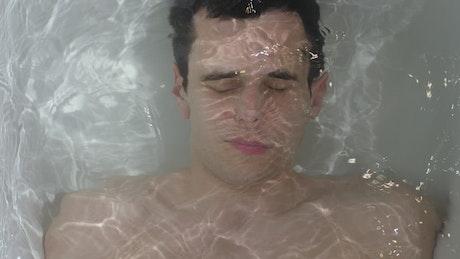 Man submerged in a bathtub, top shot