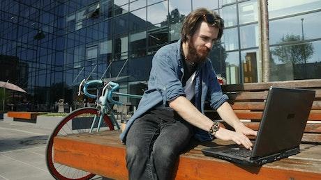Man surfs internet on laptop from street bench