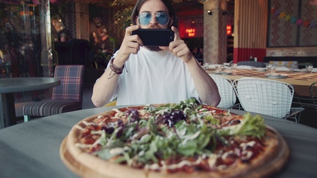 Man takes photo of pizza with mobile phone