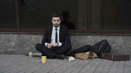 Man taking off his tie sitting on the street