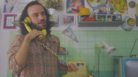 Man talking cheerfully on an old telephone
