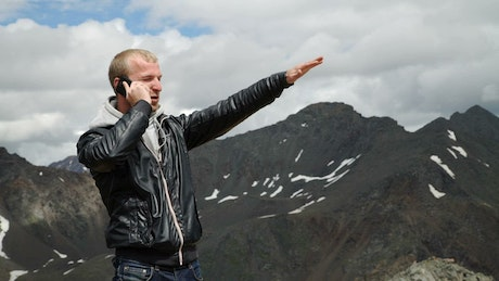 Man talking on cell phone in a mountain range