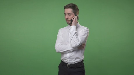 Man talking on his phone against a screen