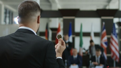 Man talking with a coin in his hand
