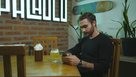 Man texting in a bar