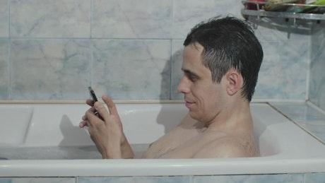 Man texting in the bathtub