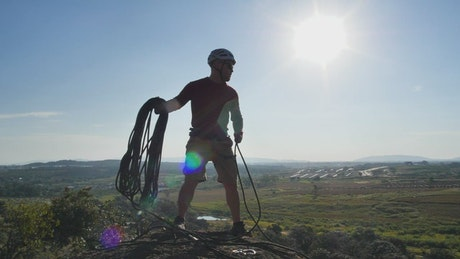 Man throwing a rope from the top of a hill